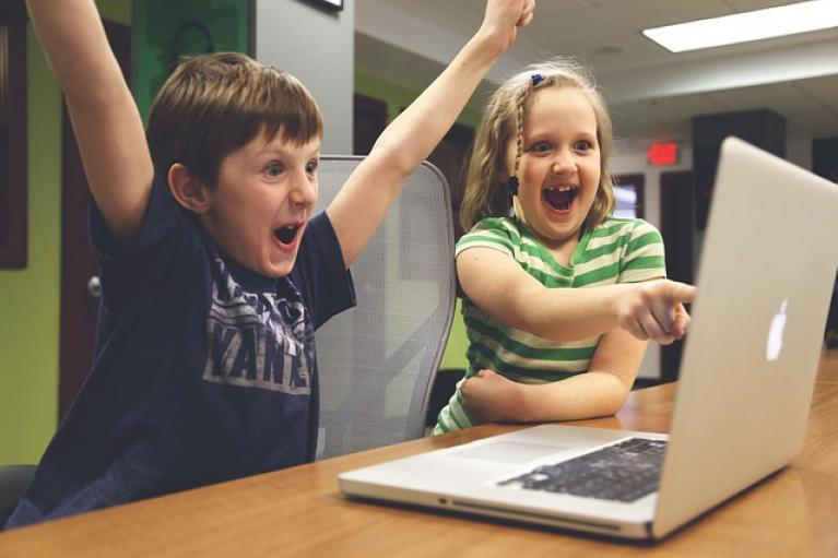 Children playing and pointing at computer